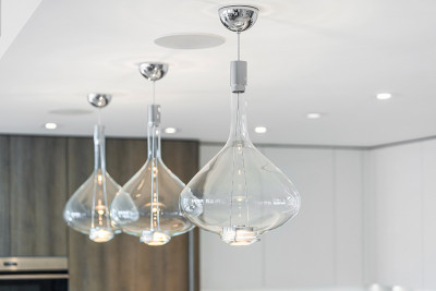 Amrit custom pedant lighting over luxuirous waterfall island in kitchen